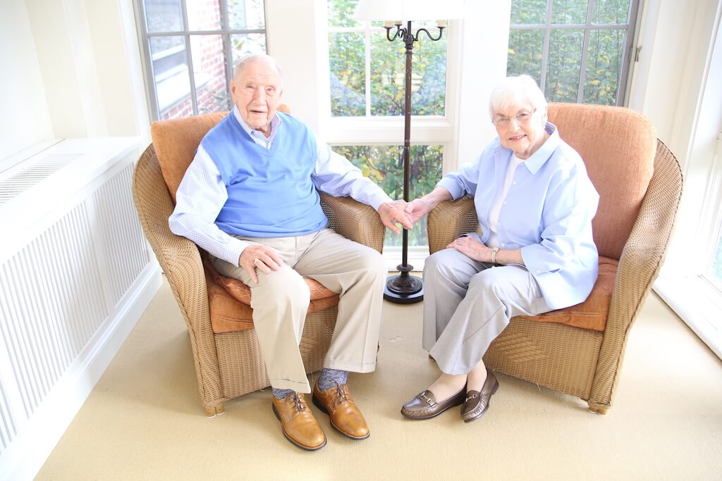 Senior couple sitting in armchairs holding hands.