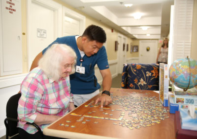 Man Helping an Elderly Woman Complete a Puzzle