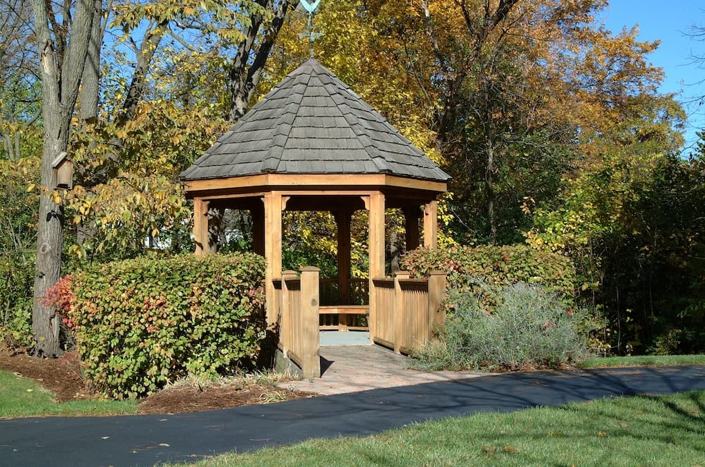 Large wooden gazebo off a walking path set within shrubs and trees.