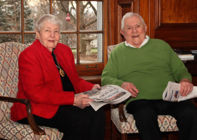 Elderly Man and an Elderly Woman Sitting in Chairs Holding Newspapers